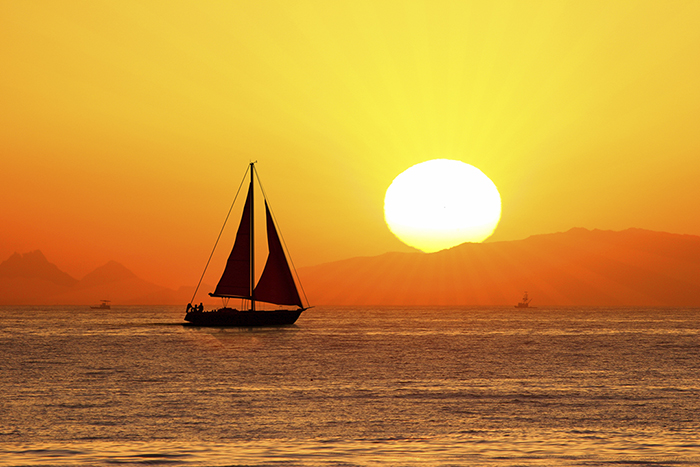 sailboat son a golden sea with bright sunrise behind