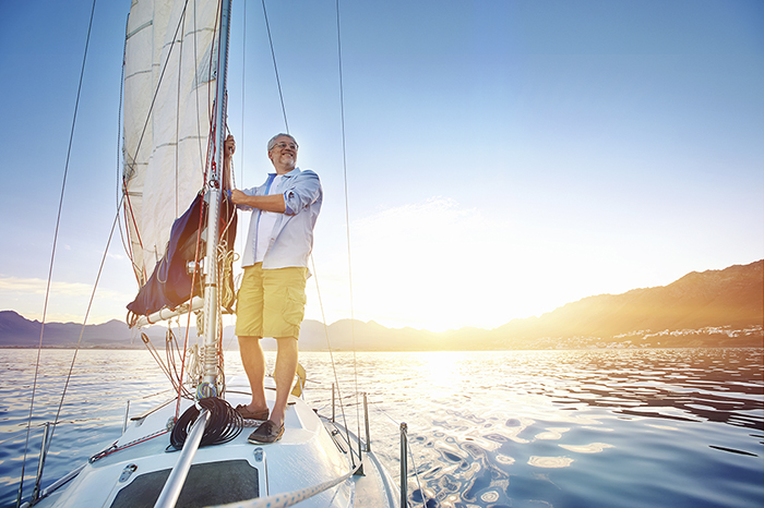 Man standing on sailboat wth the sun behind him