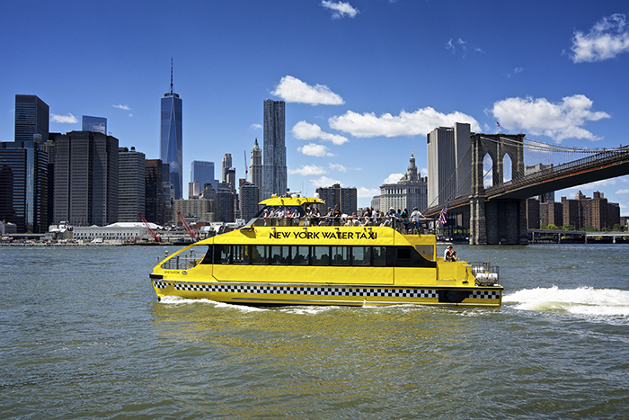 Yellow NY water taxi in front of NY skyline