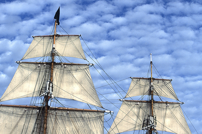 Masts and sails of a brig with puffy clouds