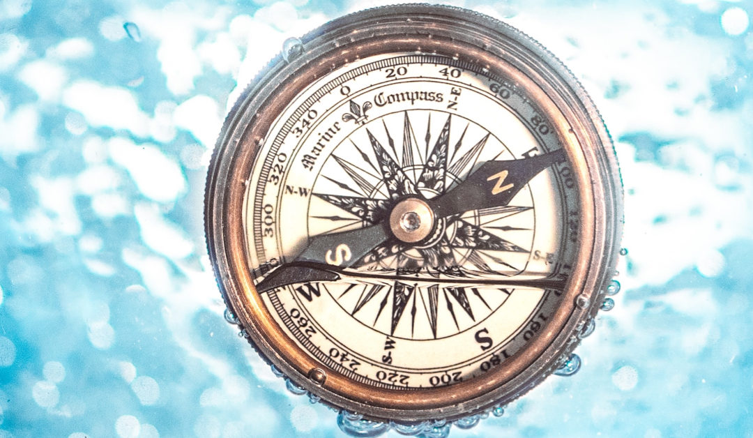 Compass floating in water background